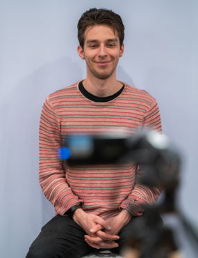 Student looking at a camera for his student ID photo