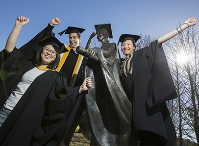 Students in graduation attire raise their arms beside a statue