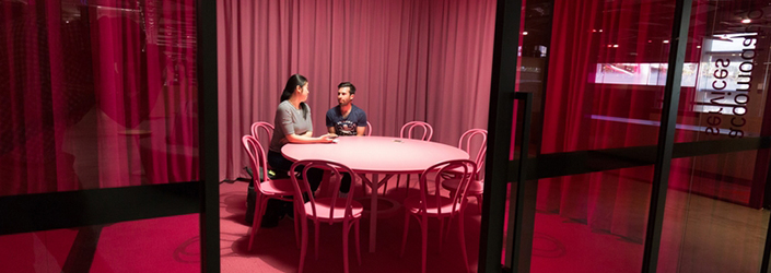 Pink room with a desk and chairs